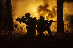 Sotilaita metsässä sotimassa